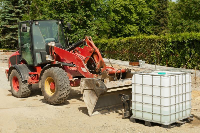 Ein roter Radlader steht neben einem Tank fuer Bauwasser