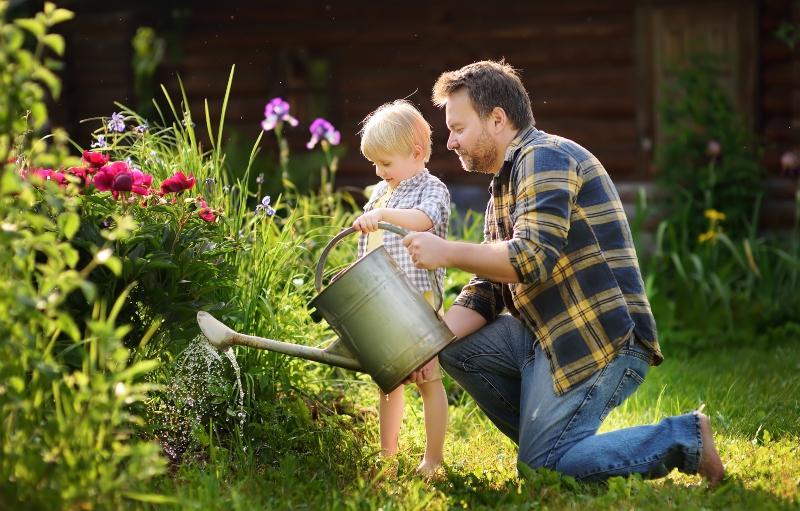 Mann gießt seinen Garten, nebendran ein kleines Kind