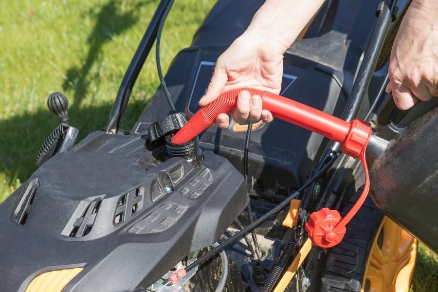 Benzin in den Tank des Diesel-Rasenmaehers giessen