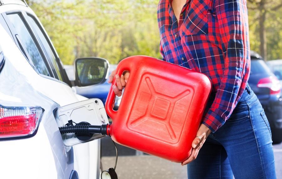 Frau mit Plastikkanister fuellt den Autotank