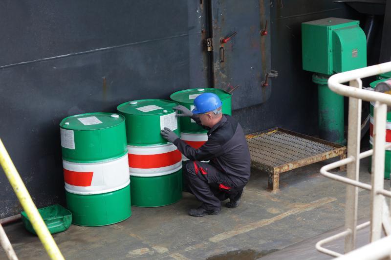 Mann prüft Beschriftung einiger Fässer was für die Zusammenlagerung von Gefahrstoffen essenziell ist