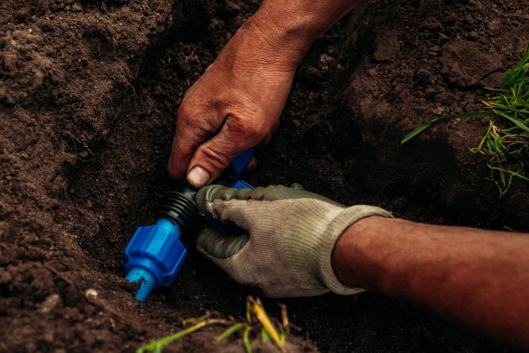 Mann installiert Bewässerungsleitungen im Boden