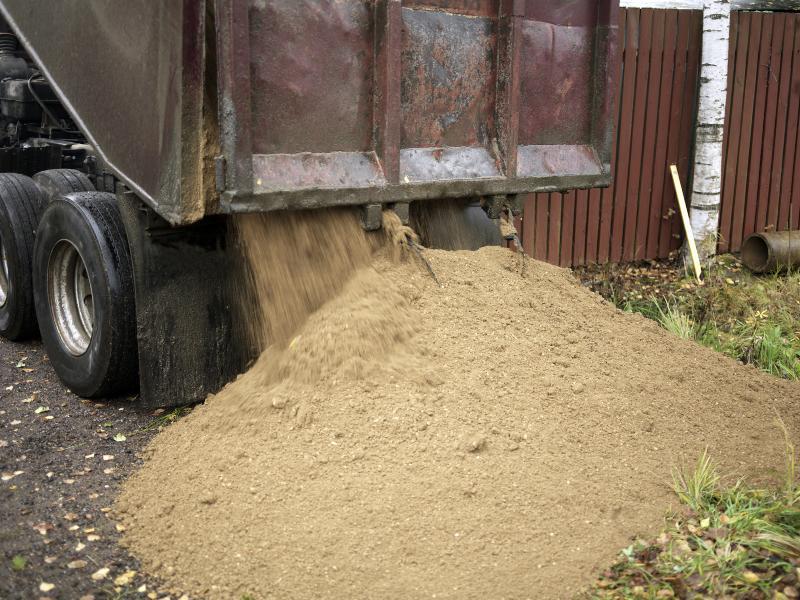 Sand wird von einem LKW abgeladen