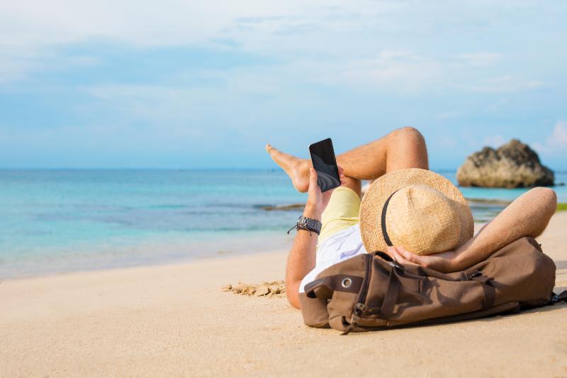 Mann mit Handy am Strand