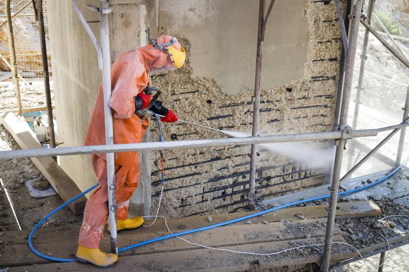 Mann benutzt Wasserstrahler auf Baustelle