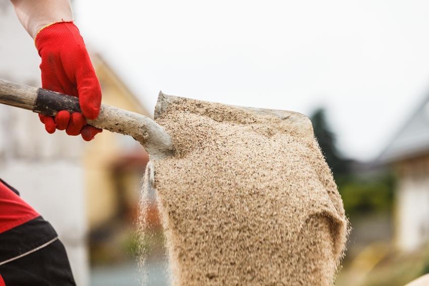 Schaufel mit Sand - beim Teich anlegen kann mithilfe von Sand ein Filter gebaut werden