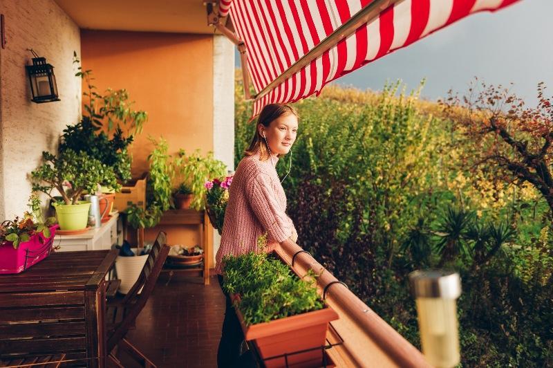 Frau auf einem Balkon mit Pflanzen