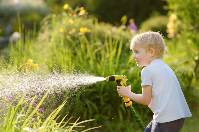 Junge versprüht Wasser mit Gartenschlauch, beispielsweise mittels IBC Container mit Schlauchanschluss