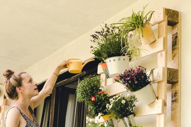 Dame gießt ihre Pflanzen