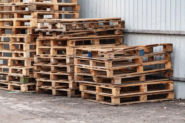 Ein Stapel beschädigter Holzpaletten - Feuchtigkeit und die Belastungen durch den Transport fordern ihren Tribut Containerpaletten aus Kunststoff