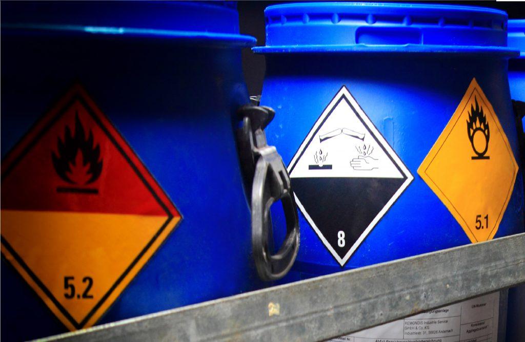 Zu sehen sind Deckelfässer, die durch entsprechende Hinweisschilder Gefahrgutbehälter gekennzeichnet sind