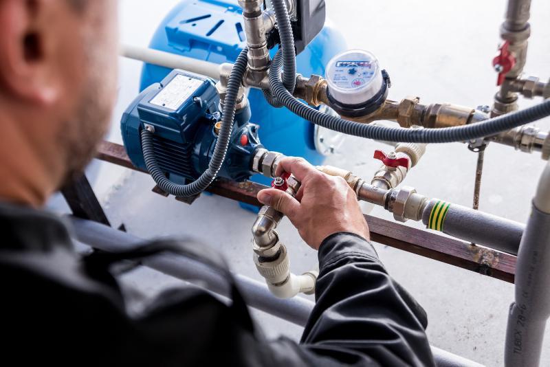 Ein Mann überprüft die Rohre und Zuflüsse eines Hauswasserwerks Hauswasserwerk oder Hauswasserautomat