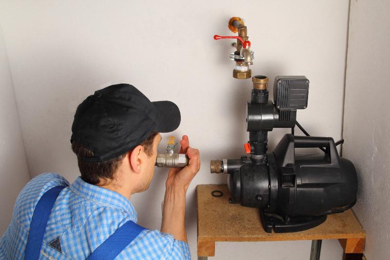 Ein Installateur montiert einen Hauswasserautomat Hauswasserwerk oder Hauswasserautomat