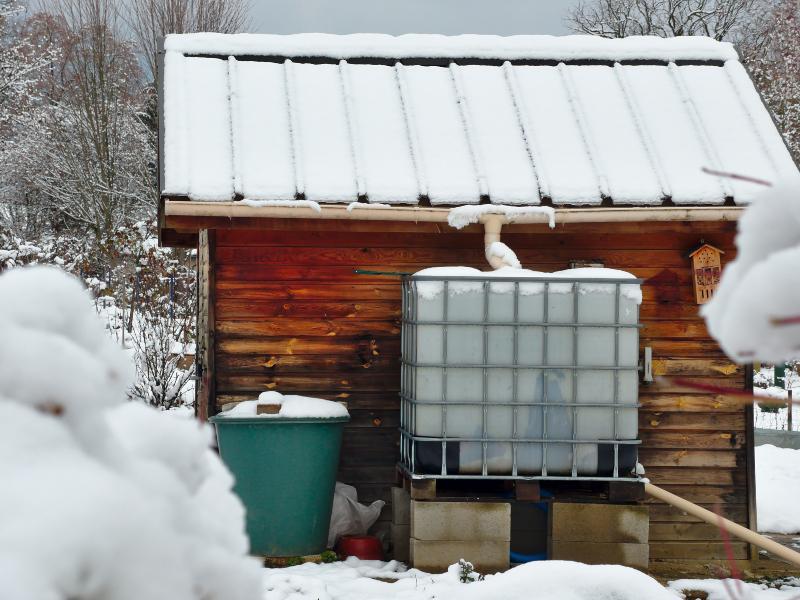 Vor einer tiefverschneiten Gartenhütte ist ein IBC-Container platziert, der an das Fallrohr angeschlossen ist. Regenwasserbehälter