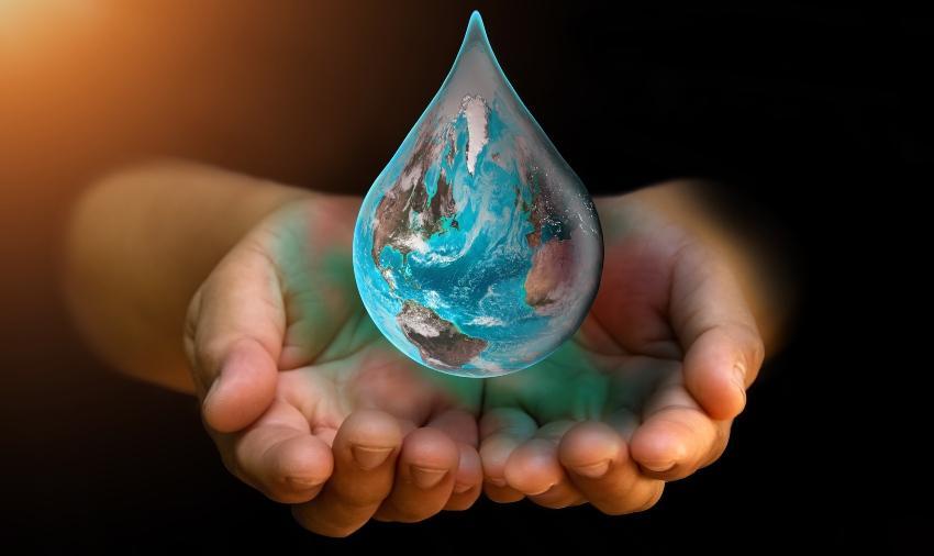 Wassertropfen fällt in Hände - Symbolbild für nachhaltige Wasserwirtschaft