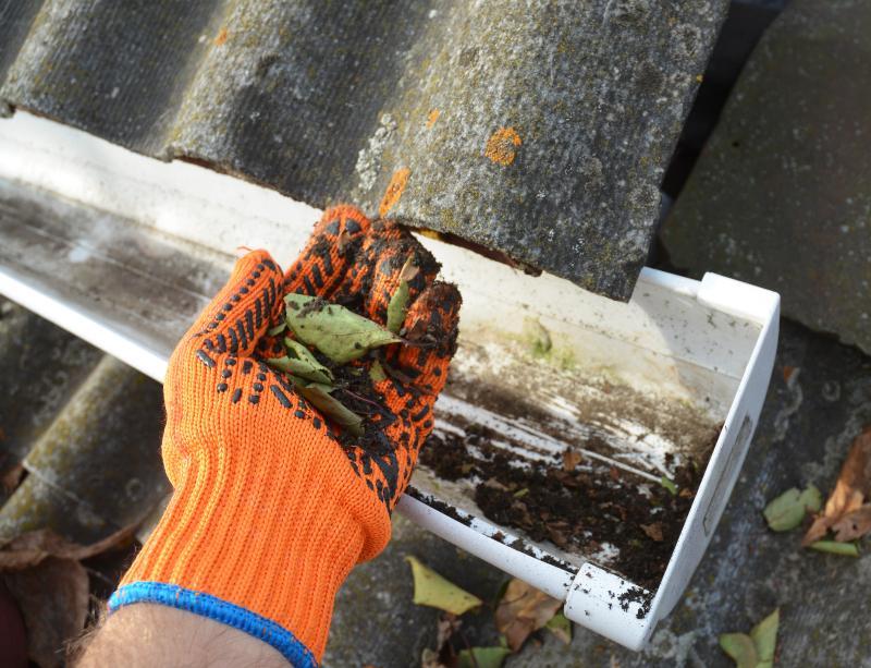 Vor einer schmutzigen Dachrinne präsentiert ein Mann eine Handvoll Schmutz und Laub, die er aus der Rinne entfernt hat.