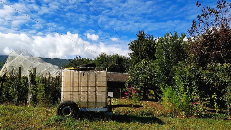 Vor einem blühenden Garten ist ein IBC-Container auf einem zweiachsigen Wagen platziert