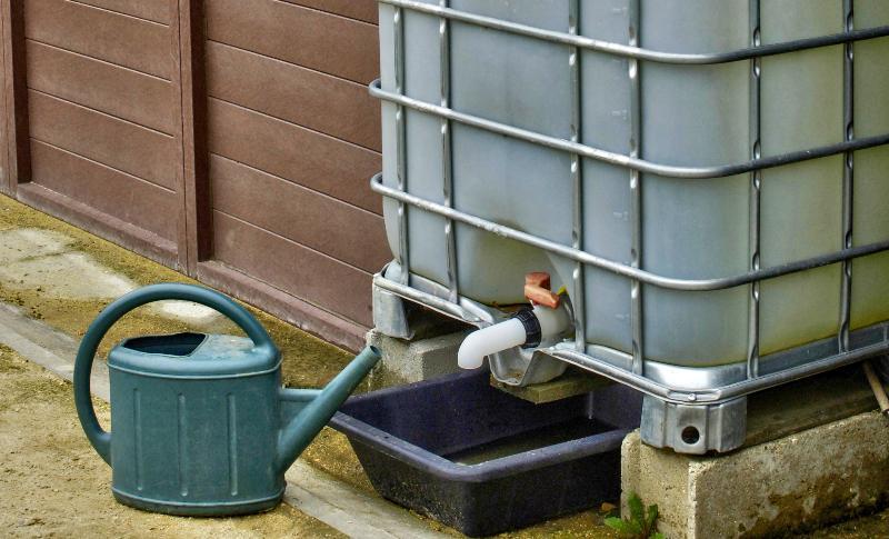 Vor einem IBC-Container mit Auslauftülle steht eine Gießkanne Distanzstück