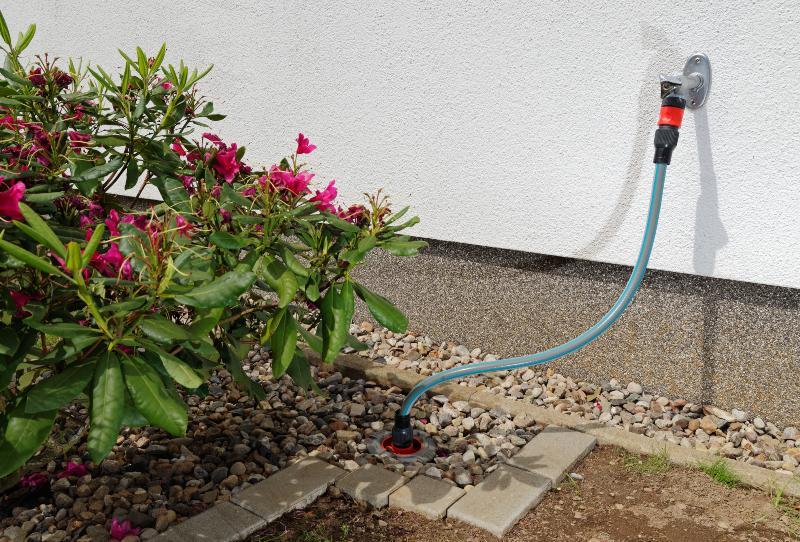 Ein Hauswasseranschluss, der die Leitungen eines Gartenbewässerungssystems speist