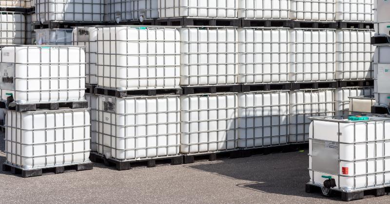 Mehrere IBC-Container sind auf einem Gewerbehof aufeinander gestapelt