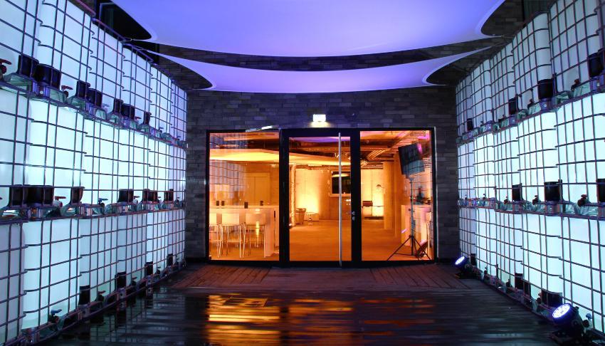Mehrere Leuchtkuben übereinandergestapelt vor dem Zugang zu einem Gebäude IBC-Tische