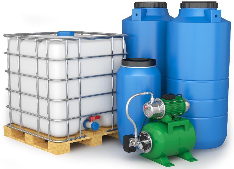 Ein IBC-Container, große Plastikfässer und ein Hauswasserwerk stehen nebeneinander
