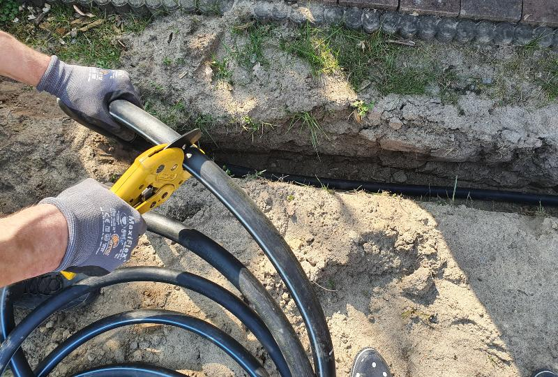 Arbeiten an einer unterirdischen Gartenbewässerung, jemand schneidet ein PE-Rohr in die passende Länge