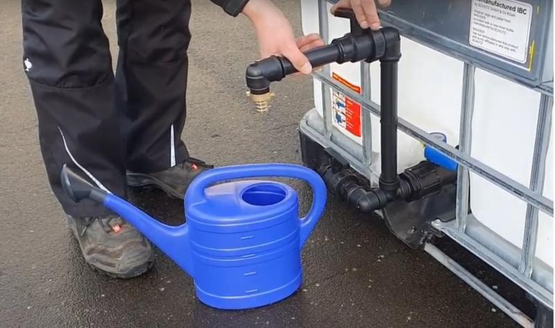 Vor einem IBC-Container mit Schwanenhals steht eine Gießkanne. Ein Mann ist damit beschäftigt, den Anschluss auf Dichtigkeit zu überprüfen. Ersatzhahn
