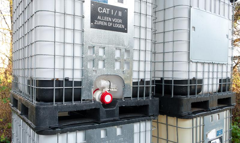 Mehrere IBC-Container die übereinander gestapelt sind, an einem ist eine auffällige, rote Hahnenkappe angebracht. Ersatzhahn