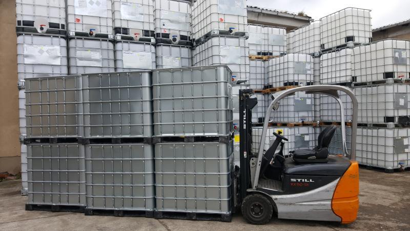 Ein Stapler ist bereit mehrere IBC-Container zu transportieren, seine Ladeholmen haben die Palette bereits gegriffen. Kombinations-IBC