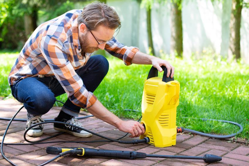 Mann schaltet Pumpe für Hochdruckreiniger ein
