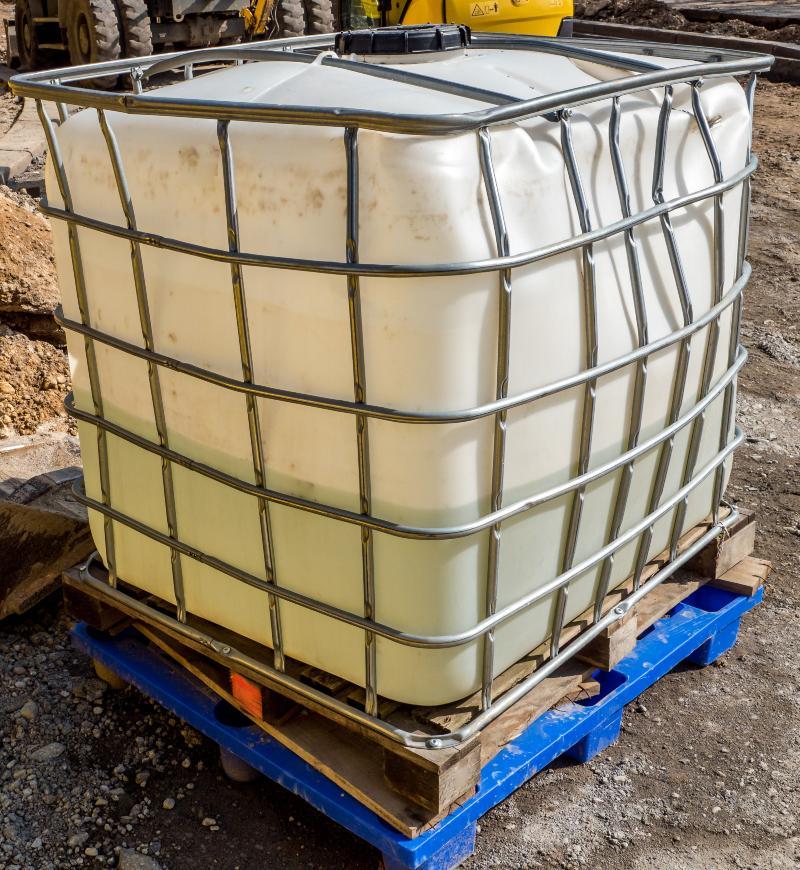 Ein IBC-Container, der im Umfeld einer Baustelle genutzt wird, hat eine sichtbare Delle, ist aber weiterhin voll funktionsfähig IBC Blase ohne Gitter
