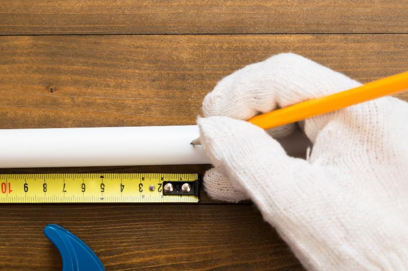 Jemand zeichnet mit einem Stift ein PVC-Rohr an der Stelle an, an der er es absägen möchte PVC Rohre verkleben