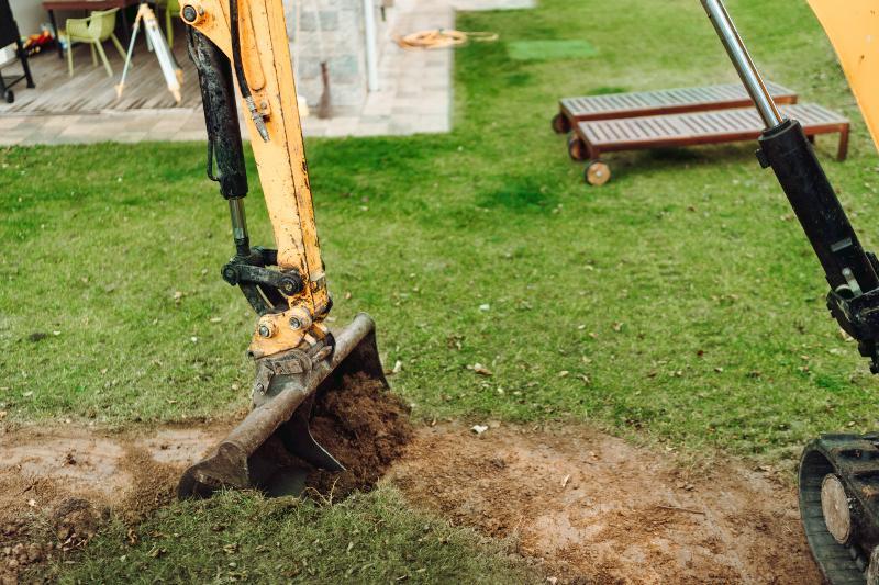 Mit einem kleinen Bagger werden Erdarbeiten in einem Garten vorgenommen Füllstandsmessung des Wassertanks