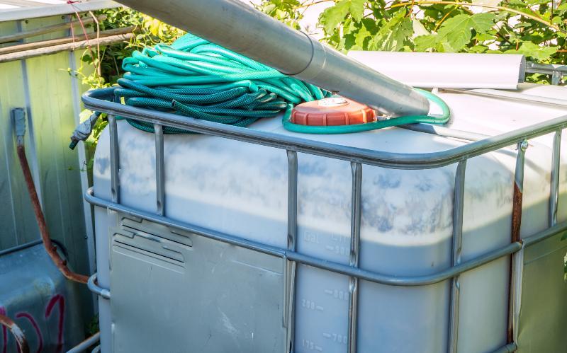 Ein IBC-Container der an ein Fallrohr angeschlossen Bewässerungsschläuche
