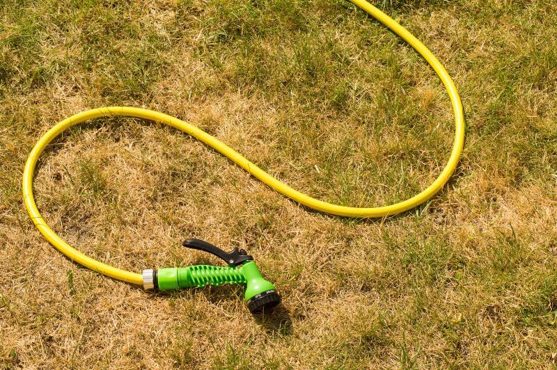 Ein Gartenschlauch liegt auf einer vertrockneten Rasenfläche
