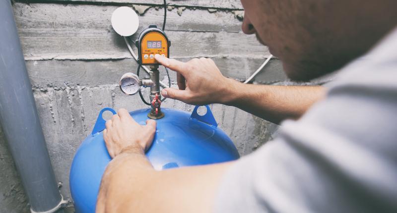 Ein Mann liest an einem elektrischen Anzeigegerät den Füllstand einer Zisterne ab Füllstandsmessung des Wassertanks