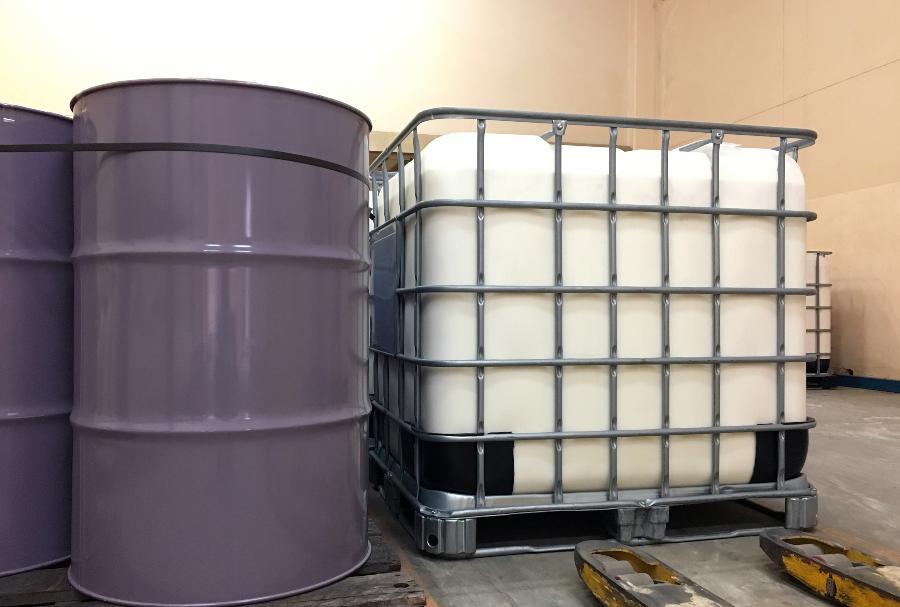 Metallfässer stehen neben einem IBC Container - Vorteile einer Fassbodenheizung