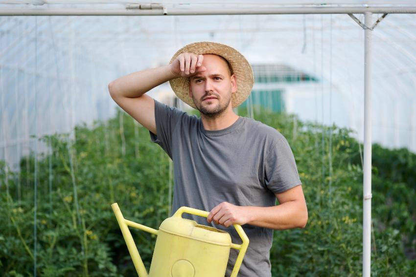 Mann mit Gießkanne wischt sich die Stirn - Automatische Pflanzenbewässerung ist angenehmer
