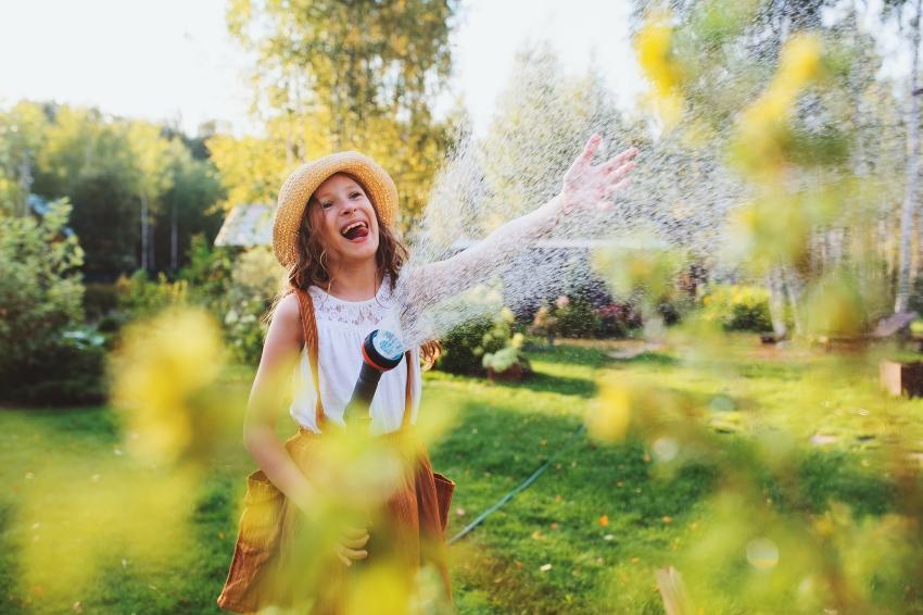 Mädchen hält fröhlich einen sprudelnden Wasserschlauch in der Hand