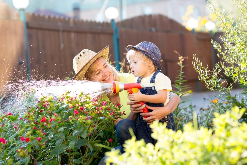 Kind gießt Blumen mit Gartenschlauch