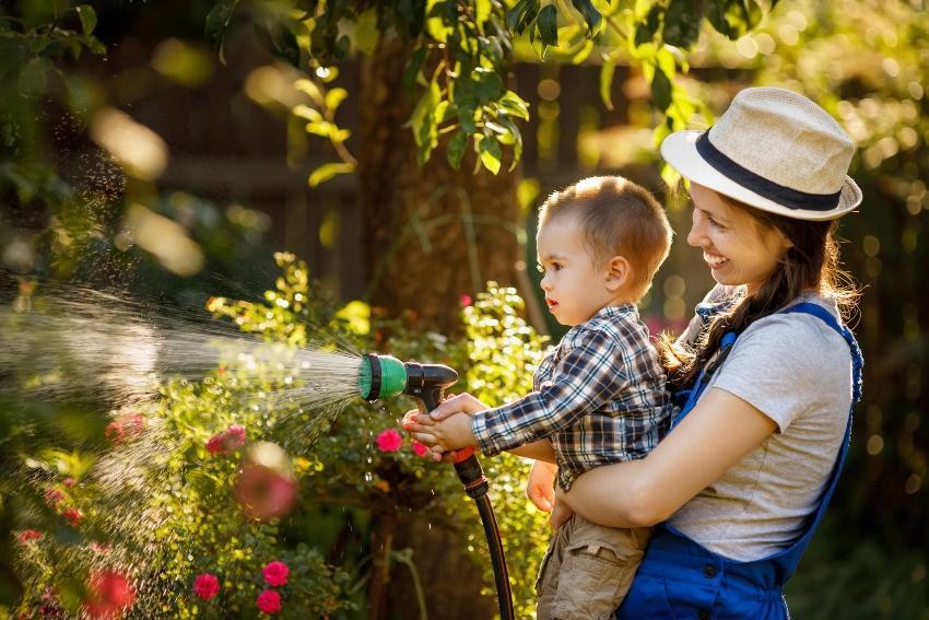 Mutter mit kleinem Kind bei der Gartenbewässerung