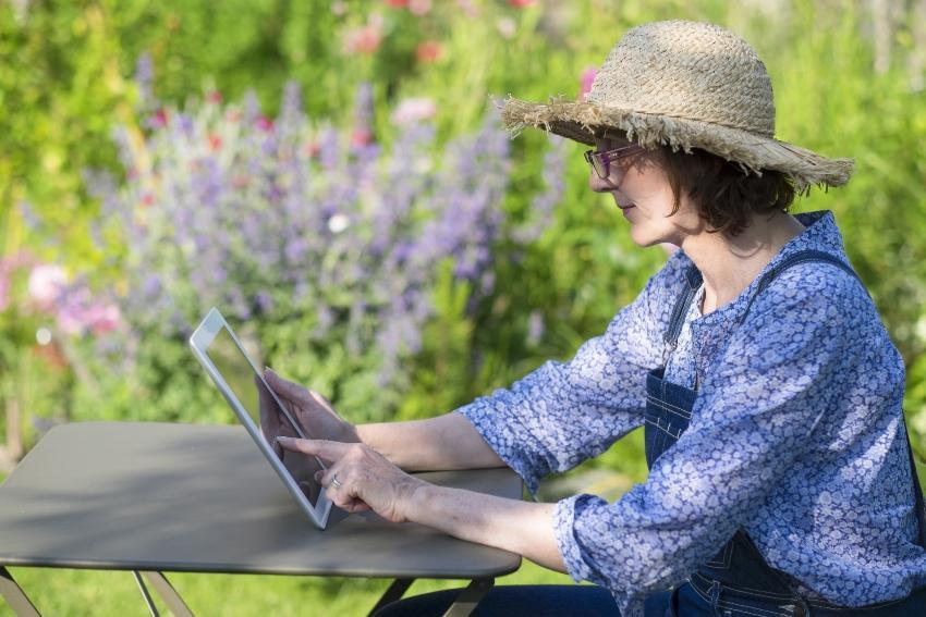 Frau im Garten mit Tablet