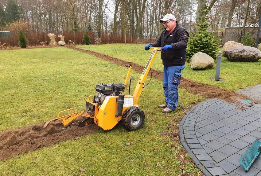 Jemand nutzt Maschine, um Gräben für Wasserleitungen im Garten anzulegen - Versenkbare Gartenbewässerung planen