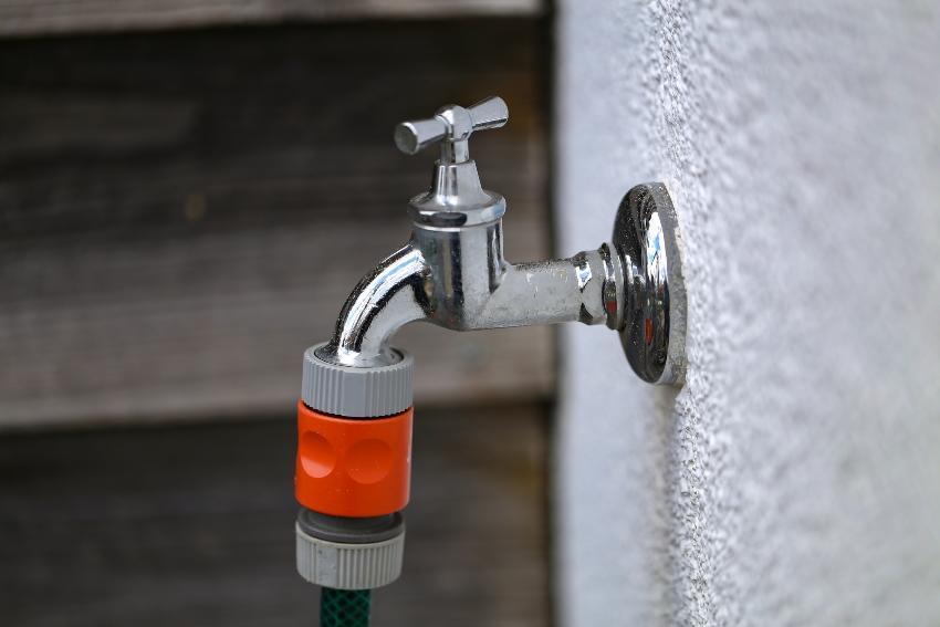 Wasserhahn mit angeschlossenem Gartenschlauch - Wasserzapfstelle