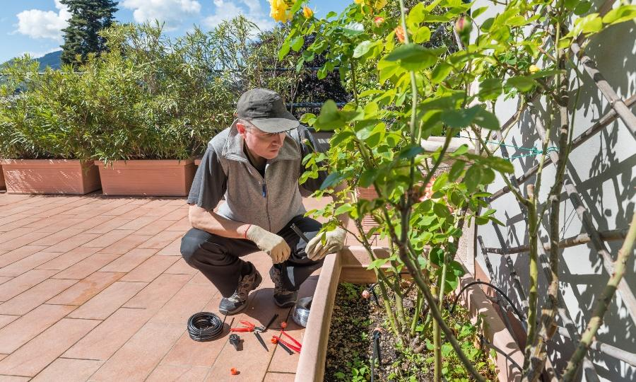 Mann installiert Tropfbewässerung auf großem Balkon / Terrasse - praktische Balkonbewässerung
