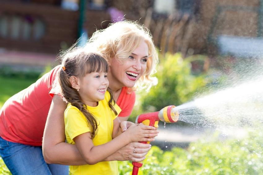 Mutter und Tochter bei der Gartenbewässerung