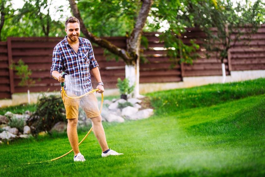 Mann bewässert seinen Rasen mit einem Gartenschlauch - er verzichtet auf Automatische Gartenberegnung