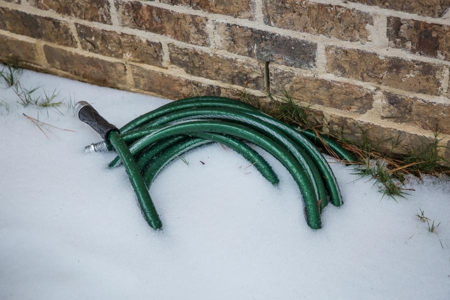 Gartenschlauch liegt im Schnee