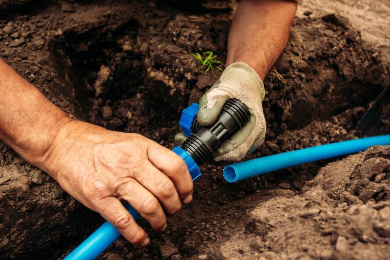 Mann verbindet unterirdische Wasserleitungen für den Garten
